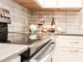 White painted maple cabinets, slate appliances, Cambria countertops, stacked Subway tile, golden champagne cabinet hardware