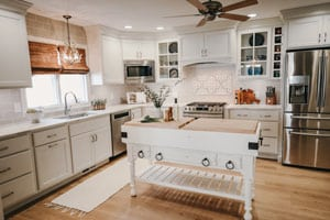 white kitchen with large island, glass display cabinets